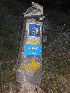 Waymark along the Camino, with sacrificial pair of boots